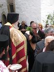 Luostarin apotti Antipas vihmoo siunatulla vedellä paikalla olijat.